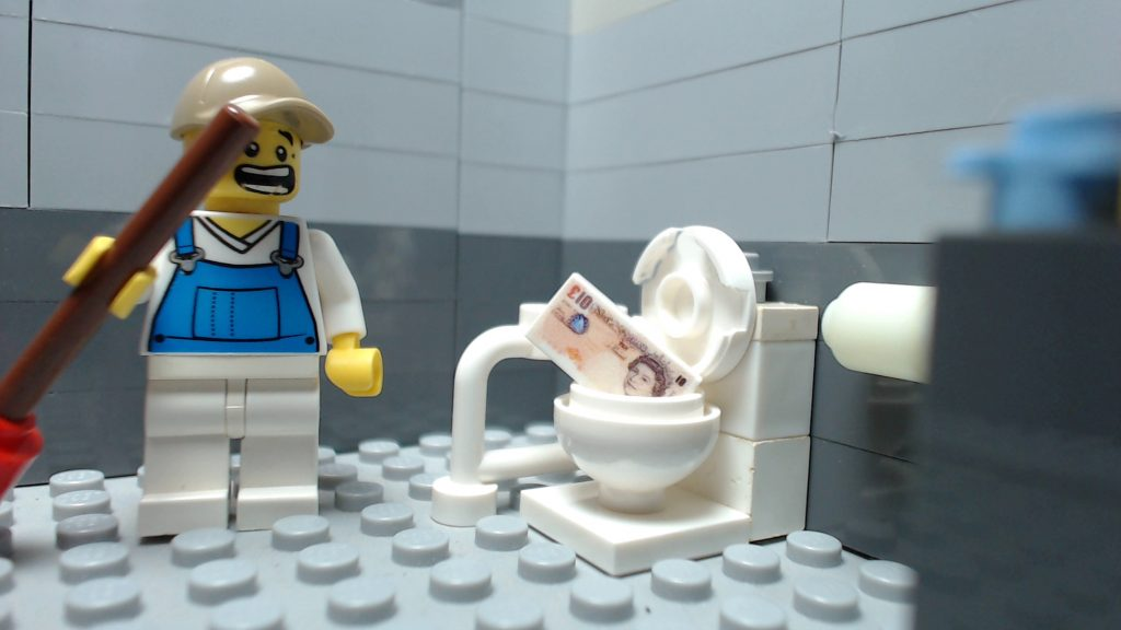 an image showing a plumber removing cash from a blocked toilet
